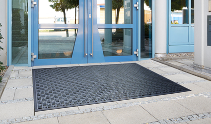 Kleen-Scrape - black Kleen-Scrape Mat with checkerboard pattern in front of the door